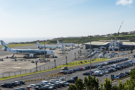 Aerial overview on João Paulo II Airport also named Aeroporto Ponta Delgada at Sao Miguel island in the Azores with airport parking lot and rental car parkings, main airport building  and planes on the airfield.  Stok Fotoğraf - 98497227