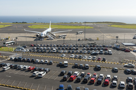 Aerial view on typical airport parking at São Miguels João Paulo II Airport, with the parking lot in the foreground and an airplane boarding in the background