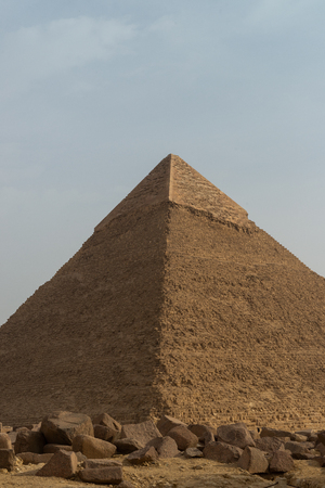 The Pyramid of Khafre or of Chephren[1] (Arabic: هرم خفرع, translit. haram ḵafraʿ, IPA: [haram xafraʕ]) is the second-tallest and second-largest of the Ancient Egyptian Pyramids of Giza and the tomb of the Fourth-Dynasty pharaoh Khafre (Chefren), who ruled from c.2558 to 2532 BC. The Giza pyramid complex is an archaeological site on the Giza Plateau, on the outskirts of Cairo, Egypt. It includes the three Great Pyramids (KhufuCheops, KhafreChephren and MenkaureMykerinos), the Great Sphinx, several cemeteries, a workers village and an industrial complex. It is located in the Western Desert, approximately 9 km (5 mi) west of the Nile river at the old town of Giza.  The pyramids, which have historically been common as emblems of ancient Egypt in the Western imagination, were popularised in Hellenistic times, when the Great Pyramid was listed by Antipater of Sidon as one of the Seven Wonders of the World. It is by far the oldest of the ancient Wonders and the only one still in existence. Stok Fotoğraf