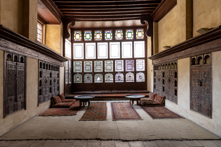 Interior room with mashrabiya windows in the Bayt Al-Suhaymi, House of Suhaymi, is an old Ottoman era house museum in islamic Cairo, Egypt. It was originally built in 1648 by Abdel Wahab el Tablawy along the Darb al-Asfar, a very prestigious and expensive