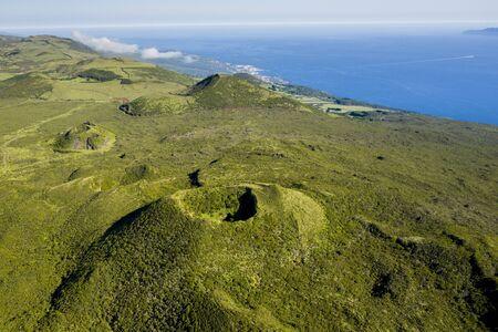 Aerial image of typical green volcanic caldera crater landscape with volcano cones of Planalto da Achada central plateau of Ilha do Pico Island, Azores, Portugal