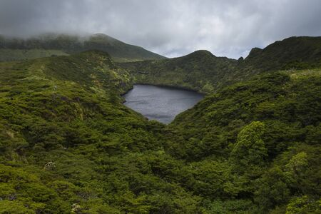 aerial image of Lagoa Comprida caldera crater lake surrounded by green vegetation and with a stormy sky on the Ilha das Flores Island at the Azores, Portugal Stok Fotoğraf