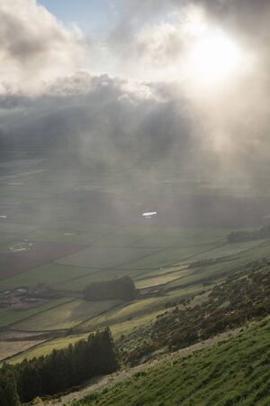 low clouds over the Miradouro da Serra do Cume revealing the typical plots with walls landscape of Terceira, Azores Stok Fotoğraf