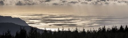 landscape panorama with pine forests, the ocean water with cloud shadows and sunlight reflection, looking down from Castelo Branco onto the nature between Ponta Garca and Ribeira Quente, Sao Miguel Island, Azores