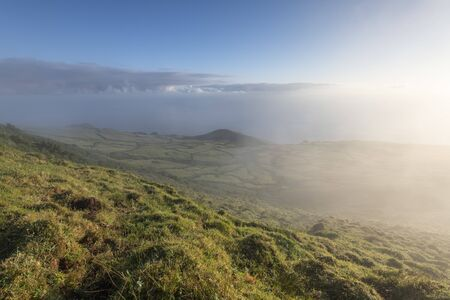 early morning landscape view with sunrise and fog on the green fields at the north coast of the Azores island of Sao Jorge, as seen from the central mountains near Pico de Esperanca, Portugal