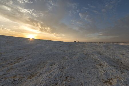 Sun rising over a white chalk or limestone plateau in the Egyptian white desert national park, Egypt