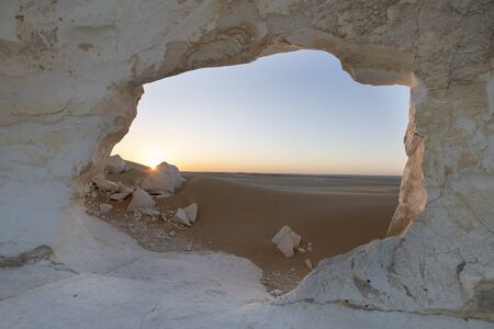 Sunset landscape when looking through the paradise gate, a typical white chalck rock formation at the White desert national park in Egypt,