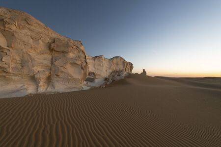 Sunset landscape at the paradise gate, a typical white chalck rock formation at the White desert national park in Egypt,