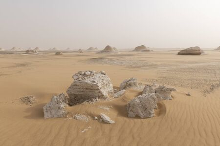 A sandstorm giving a mysterious atmosphere to the already bizarre landscape of chalck rock formations of the White Desert National Park in Egypt Stok Fotoğraf