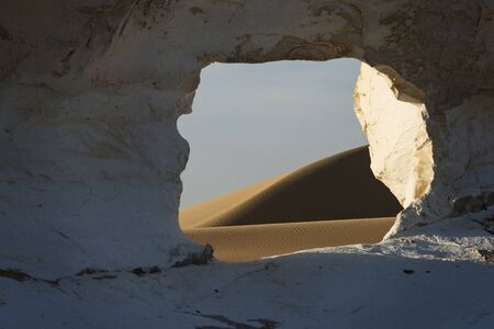 Amazing sunset landscape showing paradise window gate, a natural arch in white chalk limestone rock with desert sand dunes in the Egyptian White Desert National Park
