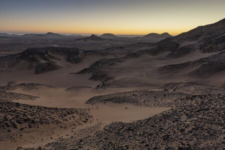 Amazing sunrise landscape in the hart of the Egyptian Black desert just south of Bahariya Oasis, an area with remarkable black volcanic hills and dolerite deposits.