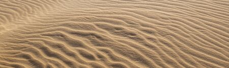Amazing abstract panoramic background image of ripples and waves in the sand in combination with low morning sunlight.  Stok Fotoğraf