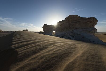 Amazing sunset landscape showing paradise gate, a natural arch in white chalk limestone rock in the Egyptian White Desert National Park Stok Fotoğraf
