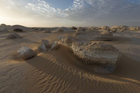 Amazing sunrise landscape with mysterious rock formations in the desert sand at the zone of el-khiyam, also named the tents, typical limestone formations in the Egyptian white desert national park Stok Fotoğraf