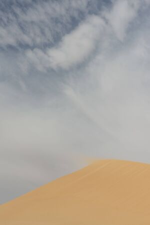 detail of blowing sand in the wind off or over the top of a sanddune, rescaping the landscape and forming new sanddunes in the Egyptian Western Desert  Stok Fotoğraf