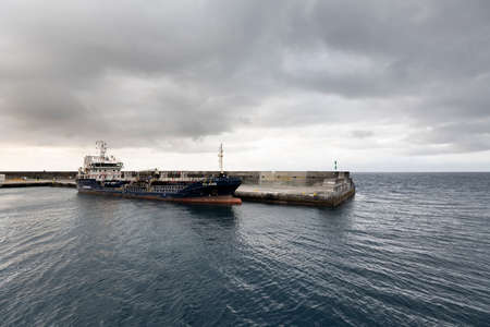 Vessel named Sao Jorge of Transinsular in the port of Sao Roque, Pico Island. This service comprises the weekly transport of containers, vehicles and general cargo between the Mainland and the islands of the Azores Archipelago (S.Miguel, Santa Maria, Terc