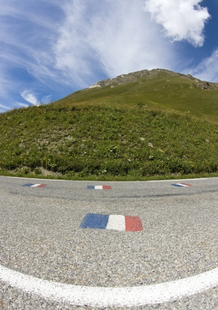 Road in mountain, french alps with french flag. Stock Photo
