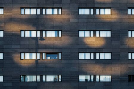 Afternoon light over the black facade of an urban building with long horizontal windows 免版税图像