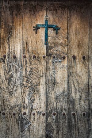 Antique wooden door decorated with a cast iron cross and iron studs