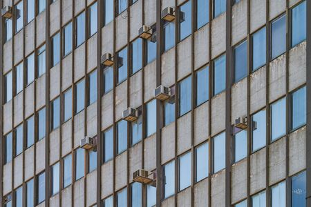 External air conditioning units hanging on the facade of an old 1964's building