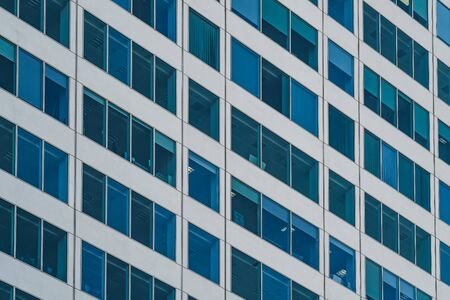Symmetrical blue windows of an office building made of aluminum and glass