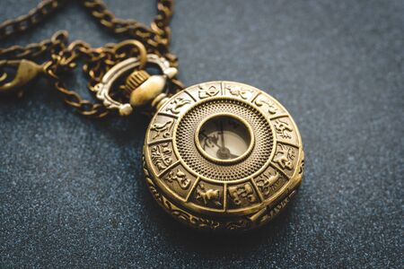 Detail of a metal pocket watch with horoscope design