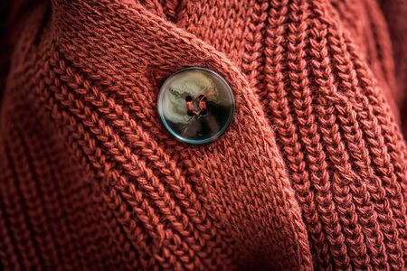 Upper button of a natural wool knitted cardigan Banco de Imagens