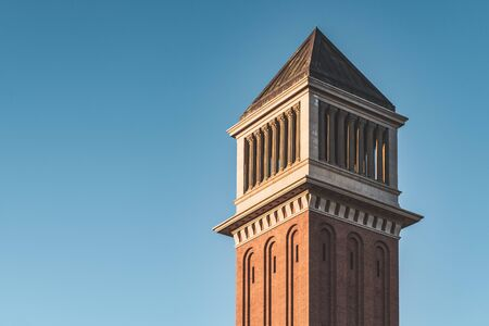 Venetian tower of Barcelona at sunset under a blue sky