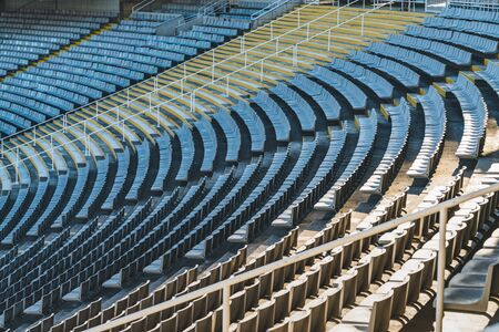 Rows of empty seats of a large stadium on sunny day before sports event 免版税图像