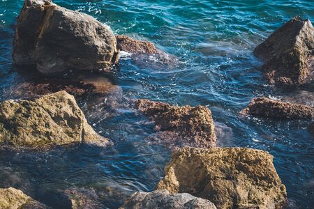 Rough rocks sticking out of transparent rippling water of blue sea on a sunny day Stock Photo