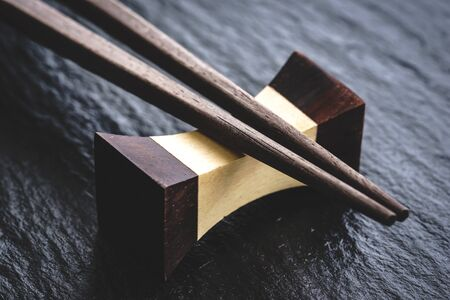 Close-up of a traditional Japanese natural wooden chopsticks resting on a hashioki over a black slate surface