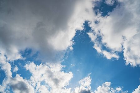 Growing cumulus clouds in a blue sky on a sunny day