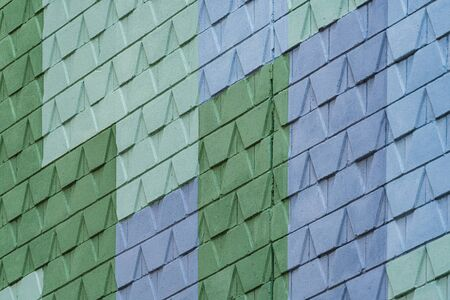 Detail of a street wall with geometric pattern design painted in blue and two different tones of green Imagens