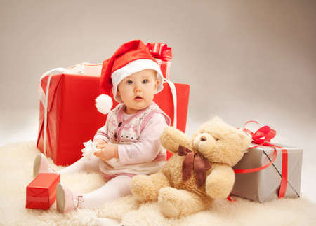 surprised baby siting with gift boxes and a teddy bear photo
