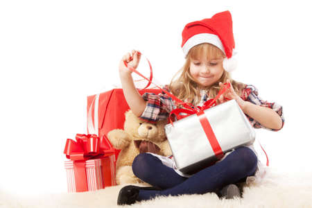unwrapping: Little girl unwrapping a christmas present Stock Photo