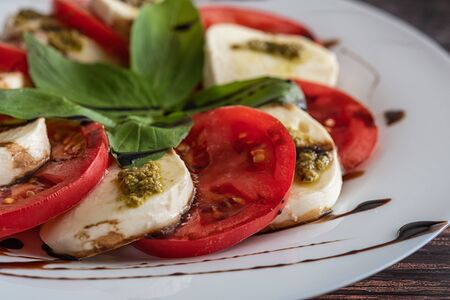 White plate of healthy classic delicious caprese salad with tomatoes and mozzarella cheese with basil leaves and strips of soy sauce on the wood background. Close up.