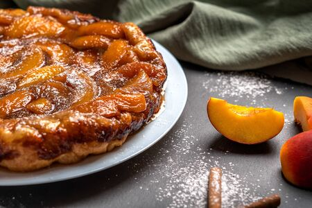 Tarte Tatin with peaches, caramel and powdered sugar close-up on a white plate on a dark background with a linen napkin. Near slices of peach and cinnamon sticks. Horizontal orientation