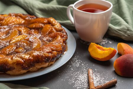 arte Tatin with peaches, caramel and powdered sugar close-up on a white plate on a dark background with a linen napkin. Next to the white Cup with black tea, peach slices and cinnamon sticks. Stock Photo