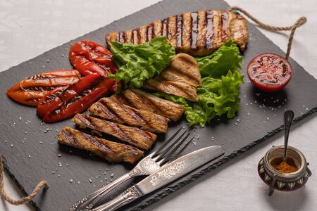 Grilled turkey breast steaks with baked peppers,lettuce and tomato on a black board with knife and fork. Next to the pepper shaker with red pepper. Horizontal orientation, close-up