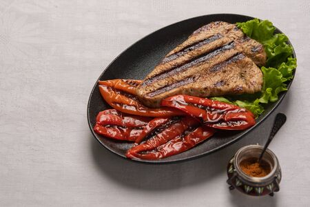 Grilled Turkey breast steak with baked peppers and lettuce leaves in a black plate on a light linen background. Next to the pepper shaker with red pepper. Horizontal orientation, copy space Фото со стока