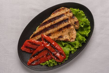Grilled turkey breast steak with baked peppers and lettuce leaves in a black oval plate on a light linen background. Horizontal orientation, top view