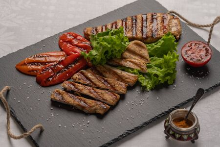 Homemade grilled turkey breast sliced steaks with baked peppers,lettuce and tomato on a black board. Next to the pepper shaker with red pepper. Horizontal orientation, close-up