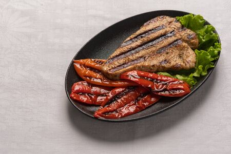 Grilled Turkey breast steak with baked peppers and lettuce leaves in a black plate on a light linen background. Horizontal orientation, copy space