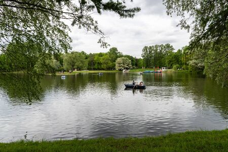 Family boating on the lake in the Park, around the trees. Horizontal orientation