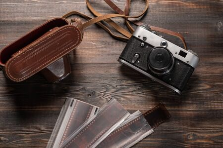 Vintage film camera with leather case and photographic film on dark wooden table. The view from the top. Old technology Stockfoto