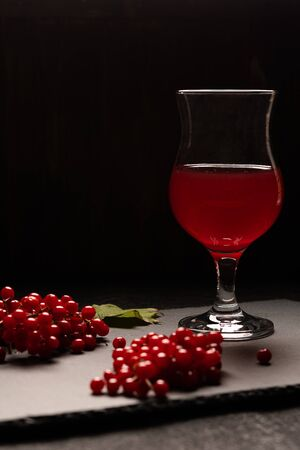 The red juice of viburnum with a stemmed glass on a black background. Near viburnum berries. Healthy food