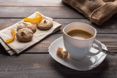 A cup of black coffee with candied oranges and lumps of sugar. Biscuits on a linen napkin and a bag of coffee