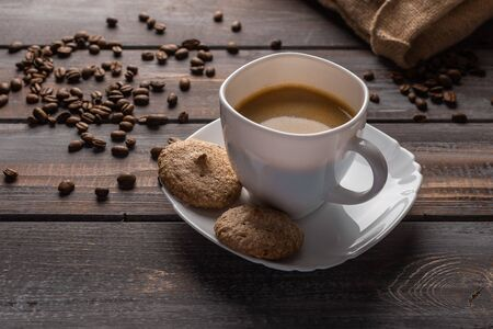 Cup of coffee and biscuits on a linen napkin. Coffee beans and bag Stok Fotoğraf