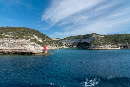 View from the yacht to the lighthouse, rocks. Blue sky with small clouds Stockfoto - 130773232