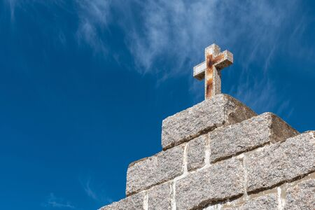 Stone cross on a blue sky background with small clouds